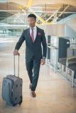 Homem de negócios novo que anda no terminal de aeroporto que leva um sui imagens de stock