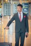 Homem de negócios novo que anda no terminal de aeroporto que leva um sui imagens de stock royalty free