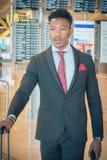 Homem de negócios novo que anda no terminal de aeroporto que leva um sui foto de stock