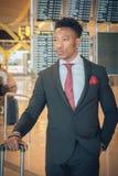Homem de negócios novo que anda no terminal de aeroporto que leva um sui imagem de stock