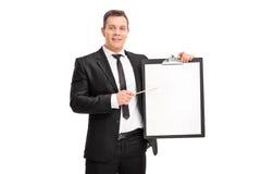 Homem de negócios novo que aponta em uma prancheta Fotos de Stock