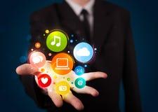 Homem de negócios novo que apresenta ícones coloridos da tecnologia Imagens de Stock Royalty Free