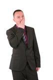 Homem de negócios novo que cobre sua boca com sua mão Fotografia de Stock