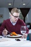 Homem de negócios novo que come em um restaurante Fotografia de Stock