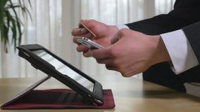 Homem de negócios novo que compra ou que usa a operação bancária em linha em um telefone esperto filme