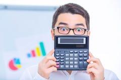 Homem de negócios novo que confirma uma calculadora Imagem de Stock