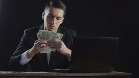 Homem de negócios novo que conta o dinheiro que senta-se na tabela no escritório Conceito do salário ou do lucro filme