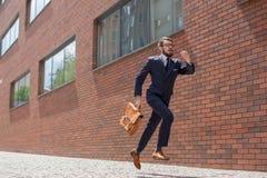 Homem de negócios novo que corre em uma rua da cidade Fotografia de Stock Royalty Free