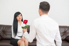 Homem de negócios novo que dá uma flor a consideravelmente Foto de Stock Royalty Free