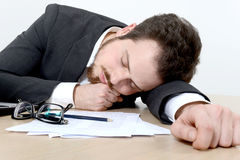 Homem de negócios novo que dorme na mesa de escritório Fotografia de Stock