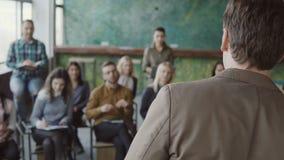 Homem de negócios novo que está na frente do grupo de jovens e de fala Conferência de negócio no escritório moderno, seminário video estoque