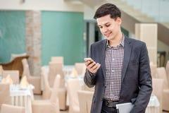 Homem de negócios novo que está no escritório e que fala no telefone Y Fotografia de Stock