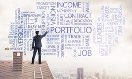 Homem de negócios novo que está no telhado da casa e que escreve a liderança Fotos de Stock Royalty Free