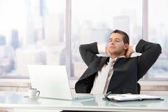 Homem de negócios novo que estica no escritório