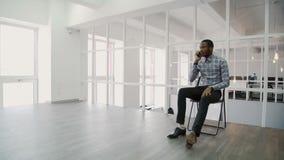 Homem de negócios novo que fala no telefone ao sentar-se no escritório moderno filme