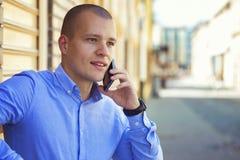 Homem de negócios novo que fala no telefone celular na rua foto de stock