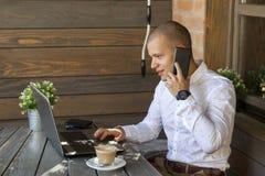 Homem de negócios novo que fala no telefone móvel fotografia de stock royalty free
