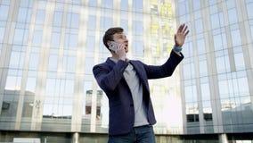 Homem de negócios novo que fala pelo móbil na cidade video estoque