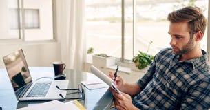 Homem de negócios novo que faz anotações em seu escritório domiciliário Imagens de Stock