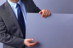 Homem de negócios novo que guarda uma placa vazia, estando no fundo cinzento Fotografia de Stock Royalty Free