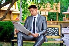 Homem de negócios novo que lê um jornal Fotos de Stock