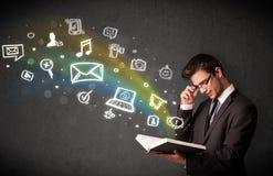 Homem de negócios novo que lê um livro com a OU de vinda dos ícones dos multimédios Foto de Stock Royalty Free