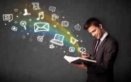 Homem de negócios novo que lê um livro com a OU de vinda dos ícones dos multimédios Fotografia de Stock Royalty Free