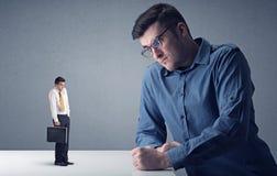 Homem de negócios novo que luta com homem de negócios diminuto imagens de stock