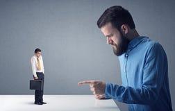 Homem de negócios novo que luta com homem de negócios diminuto fotografia de stock