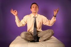 Homem de negócios novo que meditating no sofá Imagens de Stock