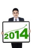 Homem de negócios novo que mostra o ano novo 2014 Imagem de Stock