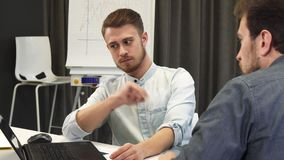 Homem de negócios novo que mostra a seu colega maduro algo no portátil filme