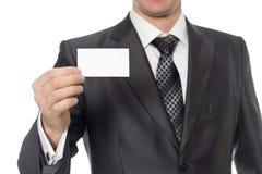 Homem de negócios novo que mostra um cartão Fotografia de Stock Royalty Free