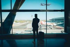 Homem de negócios novo que olha através da janela na conversa do aeroporto imagens de stock royalty free