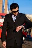 Homem de negócios novo que olha o relógio de pulso Imagem de Stock Royalty Free