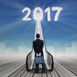 Homem de negócios novo que olha os números 2017 com escada rolante Foto de Stock