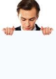 Homem de negócios novo que olha para baixo no quadro de avisos em branco Foto de Stock Royalty Free
