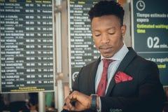 Homem de negócios novo que olha seu relógio esperto no aeroporto em f fotografia de stock