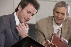 Homem de negócios novo que olha um dobrador fotos de stock royalty free
