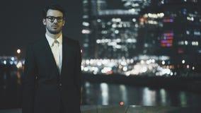Homem de negócios novo que põe sobre vidros e que olha uma arquitetura da cidade na noite Imagem de Stock