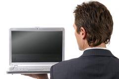 Homem de negócios novo que presta atenção no portátil Fotografia de Stock Royalty Free