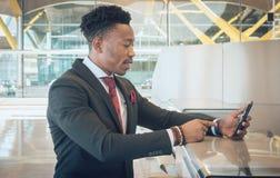Homem de negócios novo que procura seu celular na verificação imagem de stock royalty free