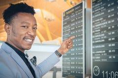 Homem de negócios novo que procura seu voo a Barcelona no ar fotografia de stock royalty free