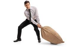 Homem de negócios novo que puxa um saco de serapilheira fotografia de stock royalty free