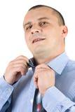 Homem de negócios novo que repara seu laço isolado no branco Foto de Stock