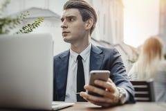 Homem de negócios novo que senta-se ao lado do portátil e que guarda o telefone celular à disposição foto de stock royalty free