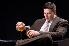 Homem de negócios novo que senta-se em um sofá com uma bebida alcoólica Fotos de Stock Royalty Free