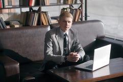 Homem de negócios novo que senta-se na mesa com portátil Foto de Stock