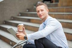 Homem de negócios novo que senta-se nas escadas com a bicicleta que mantém o copo e a tabuleta de café do papel que tomam um rest fotografia de stock royalty free