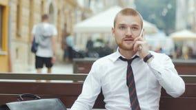 Homem de negócios novo que senta-se no banco que trabalha no acordo e que fala no telefone celular vídeos de arquivo